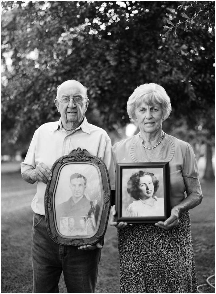 Elderly couple hold portraits of themselves at a younger age.